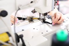 Occupation needlewoman. Seamstress sewing on the sewing machine in the manufacturing plant Royalty Free Stock Images