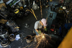 Occupational safety in heavy industry. Bangkok, Thailand – March 30, 2015. Man at work. A man doing his welding job without wearing face protection in workshop Stock Photos