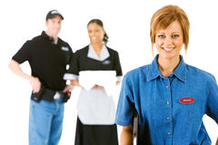 Occupations: Happy Server with Others Behind. Extensive series featuring a multi-ethnic group of people in various occupations.  Includes policeman, housekeeper Stock Photo