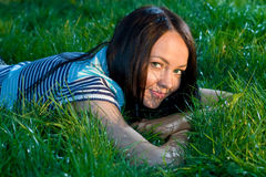Occupations on the nature 2. Girl sits on a green grass and writes on a paper Royalty Free Stock Photo