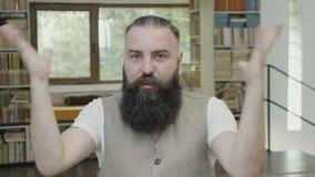 Occupi della reazione saltata di giovane uomo attraente di affari con la barba che si siede nell'ufficio - stock footage