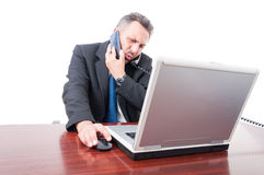 Occupied broker using both telephone and mobile phone. In his office isolated on white background Stock Photography