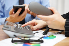 Occupied business people in office are dialing on land line tele. Phone and and using mobile smart phone Royalty Free Stock Photography