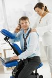 Occupied businessman getting massage. Businessman talking on mobile while getting neck massage in office stock photos