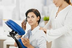 Occupied businesswoman getting massage stock photos
