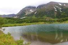 Lake Tahkoloch lies at the base of the extinct Vachkazhets volcano on the Kamchatka Peninsula, Russia. It occupies the entire extinct volcano basin 150 meters stock photos