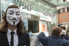Occupy Exeter activist wearing Guy Fawkes mask. An Occupy Exeter activist wearing a Guy Fawkes mask outside the Exeter branch of Topshop Royalty Free Stock Photography