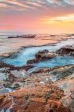 Oceaan die in kustdiekanalen stromen in rots en een overweldigende zonsopgang worden geërodeerd royalty-vrije stock fotografie