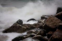 Oceaan die rotsen met strengh raken stock fotografie