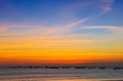 Oceaan kustzonsondergang en vissersboten Stock Afbeeldingen