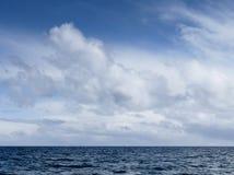 Oceaan met blauwe hemel en witte wolken Stock Fotografie