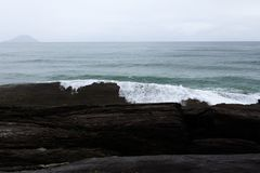Oceaan met golven die in stenen verpletteren stock afbeelding
