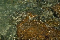 Oceaan ondiep water met de rotsachtige oppervlakte van het kust onderwater tonende abstracte patroon stock fotografie