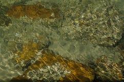 Oceaan ondiep water met de rotsachtige oppervlakte van het kust onderwater tonende abstracte patroon stock foto