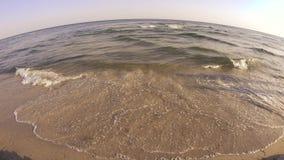 Oceaangolf die omhoog op een zandig strand rollen stock videobeelden