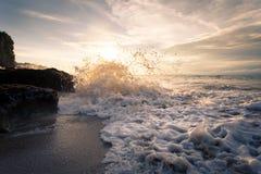 Oceaangolf met schuimafstraffing tegen de rotsen bij zonsondergang Royalty-vrije Stock Foto's