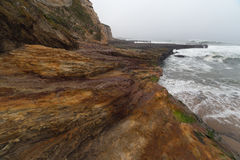 Oceaangolven die neer op gestreepte kustrotsen stromen Stock Foto's