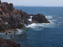 Oceaangolven die op de rotsachtige kust van verharde lava met holen en holten breken Bergen en vulkanen op de horizon royalty-vrije stock foto