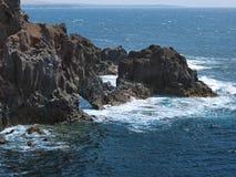 Oceaangolven die op de rotsachtige kust van verharde lava met holen en holten breken Bergen en vulkanen op de horizon stock foto