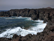 Oceaangolven die op de rotsachtige kust van verharde lava met holen en holten breken Bergen en vulkanen op de horizon royalty-vrije stock afbeelding