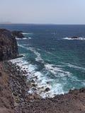 Oceaangolven die op de rotsachtige kust van verharde lava met holen en holten breken Bergen en vulkanen op de horizon stock afbeeldingen