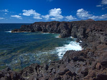 Oceaangolven die op de rotsachtige kust van verharde lava met holen en holten breken Diepe blauwe hemel met witte wolken en berge stock foto's