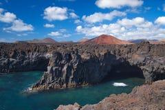 Oceaangolven die op de rotsachtige kust van verharde lava met holen en holten breken Diepe blauwe hemel met witte wolken en berge stock afbeelding