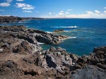 Oceaangolven die op de rotsachtige kust van verharde lava met holen en holten breken Diepe blauwe hemel met witte wolken en berge royalty-vrije stock foto