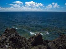 Oceaangolven die op de rotsachtige kust van verharde lava met holen en holten breken Diepe blauwe hemel met witte wolken op de ho royalty-vrije stock foto
