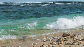 Oceaangolven die op het zandstrand omwikkelen met sommige stenen Riffgolven op achtergrond stock videobeelden