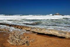 Oceaangolven die op vlotte rotsen op het tijdstip van eb lopen. Royalty-vrije Stock Afbeeldingen