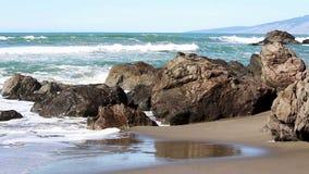 Oceaangolven die Rotsen op Sandy Beach raken stock videobeelden
