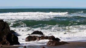 Oceaangolven die Rotsen op Sandy Beach Surfer In Background raken stock videobeelden