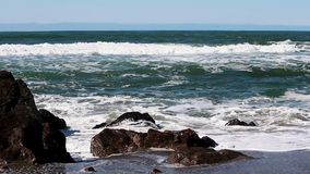 Oceaangolven die Rotsen op Sandy Beach Surfer In Background raken stock video