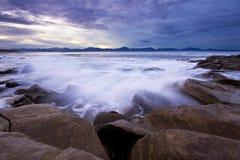 Oceaangolven die tegen de rotsen bij zonsondergang bespatten Royalty-vrije Stock Fotografie