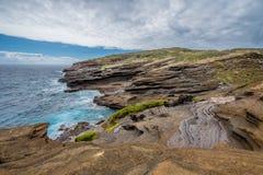 Oceaangolven die tegen de unieke vormingen van de lavarots van het Lanai-Vooruitzicht op Oahu, Hawaï verpletteren stock foto's