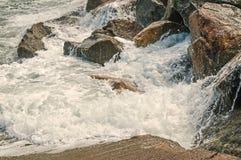 Oceaangolven die tegen rotsachtige oever breken Royalty-vrije Stock Afbeeldingen