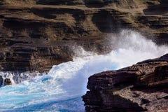 Oceaangolven die tegen rotsen en klippen met wit schuimcl verpletteren stock afbeeldingen