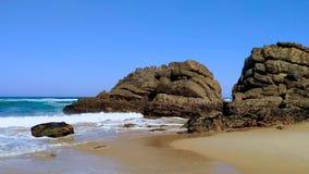 Oceaangolven die tegen rotsen op zandig strand op Atlantische kust van Portugal verpletteren stock footage
