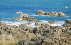 Oceaangolven en rotsen in water Stock Afbeelding