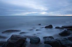 Oceaangolven en water die over rotsachtige pier meeslepen stock foto's