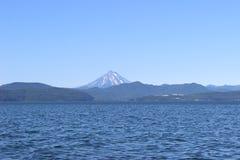 Oceaangolven met een vulkaan op de horizon Stock Foto
