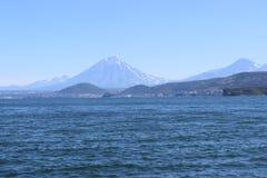 Oceaangolven met een vulkaan op de horizon Stock Fotografie