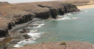 Oceaangolven op rotsachtige kust met zwart zand van Papagayo-stranden op het Eiland Lanzarote, Canarische Eilanden, Spanje stock videobeelden