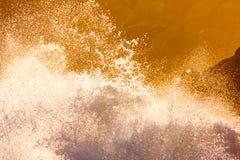 Oceaangolvenneerstorting tegen Rotsen bij Schemer stock afbeelding
