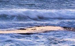 Oceaangolvenplons over kalme rotsplank bij dageraad Royalty-vrije Stock Foto's