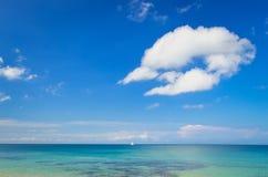 Oceaanlandschap met blauwe bewolkte hemel en zeilboot Stock Foto's