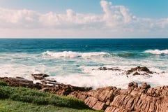 Oceaanstrand in Margate, SA, blauwe hemel, witte wolken, turkooise golven, rotsen Royalty-vrije Stock Afbeelding