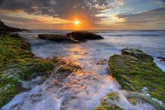 Oceaanstromen rond de rotsen bij Bungan-Strand Stock Foto