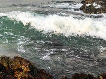 Oceaanstroom tussen rotsen stock afbeeldingen